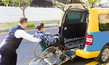 man duwt rolstoelgebruiker in de auto