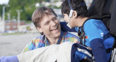 vader lacht naar zoon in de rolstoel