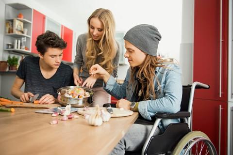 een begeleider helpt twee jongjvolwassenen met koken