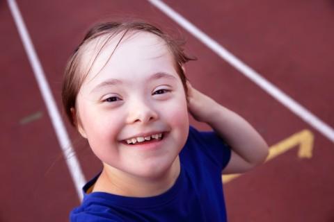 meisje met syndroom van down op de atletiekpiste, lachend kijkend in de camera